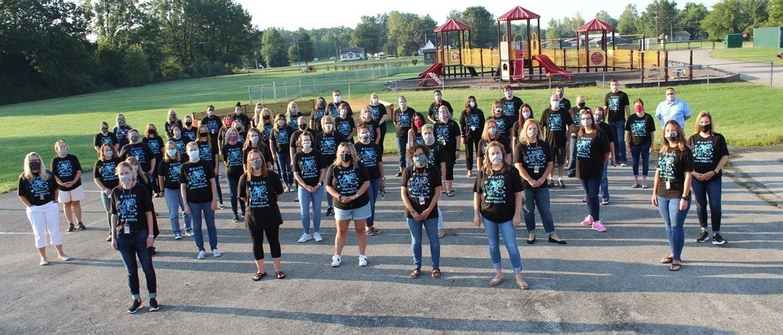 School Staff standing in masks outside.